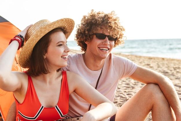 屋外のビーチに座っている若いかわいい愛情のあるカップルの友人の写真