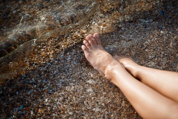 朝のビーチで若い女の子の足の写真
