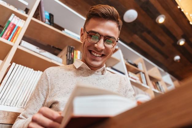 Изображение молодого счастливого человека в очках, одетых в рубашку, сидя в кафе во время чтения книги. посмотри книгу.