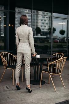 スタイリッシュなスーツ、後ろ向きの白い靴で黒髪の若い素敵な白人女性の写真