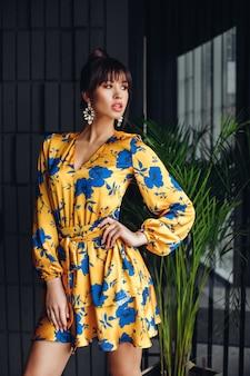 黄色と青のドレスを着た黒髪の若い素敵な白人女性の写真、金色の靴はカメラのさまざまなポーズを示しています