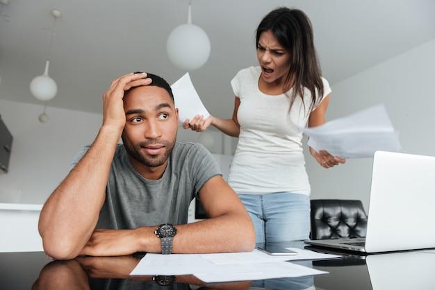 Картина молодая влюбленная пара обсуждает домашние счета дома. женщина кричала мужчине, держа документы.