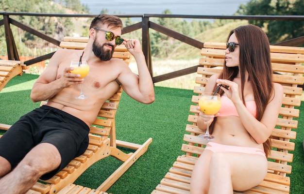 Фото молодой мужчина и женщина, лежа на шезлонгах и посмотреть друг на друга. они носят купальные костюмы и солнцезащитные очки. люди выглядят счастливыми и довольными.