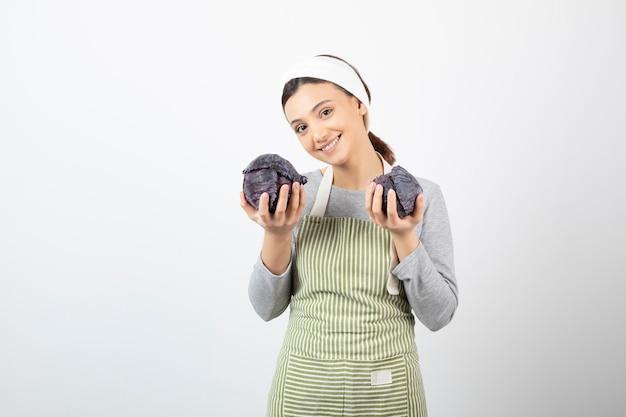 두 개의 보라색 양배추를 들고 웃는 젊은 주부의 사진