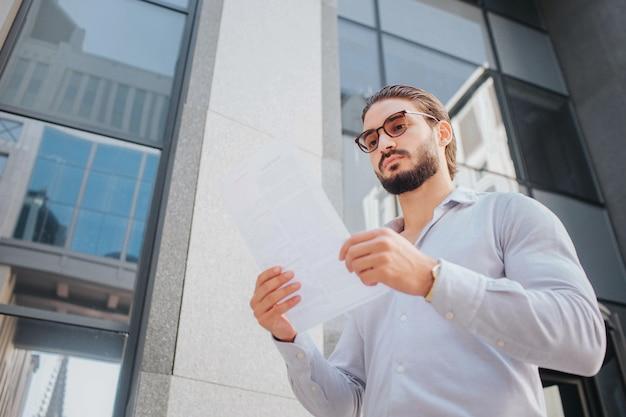세련 된 젊은이의 그림 스탠드와 포즈. 그는 선글라스를 통해 흰 종이를 봅니다. 남자는 침착하고 평화 롭고 집중적입니다. 그는 유리 건물 앞에 서 있습니다.