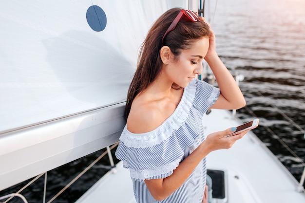 젊은 여자의 그림은 서서 기댄다. 그녀는 빨간 안경을 손에 들고 다른 손에 전화를합니다. 갈색 머리는 심각하고 집중적입니다.