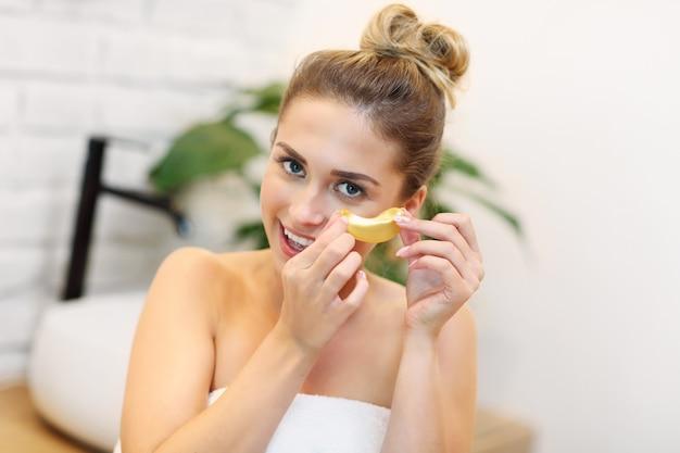 浴室で化粧品を使用している若い女性の写真