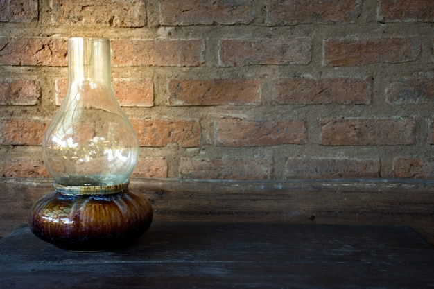 Picture of oil lamp at night on a wooden table with old brick wall background