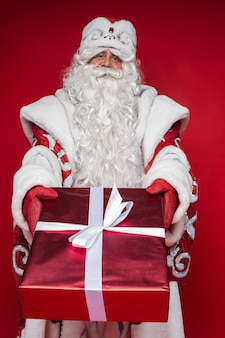 Picture of an old caucasian father frost in long warm coat, red mittens and a hat holds a christmas present