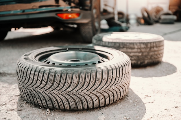 Picture of old tire on ground at auto mechanic workshop. in background car.