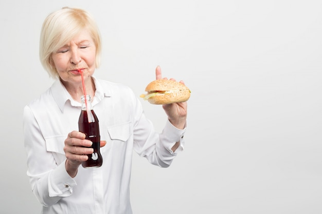 A picture of old woman tasting coca cola and eating a burger. she doesn't like to have a healthy lifestyle. she prefers to eat tasty but fattening and bad food.