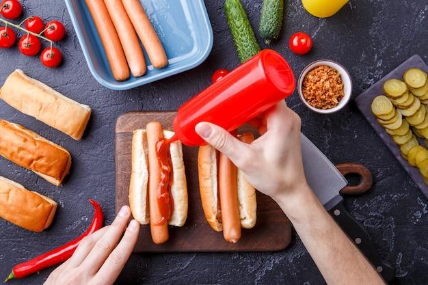 ホットドッグ、まな板、男の手のための食材をテーブルの上の写真