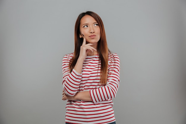 Picture of pensive asian woman in sweater looking up over gray background