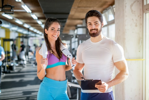Picture of personal fitness trainer and his female client in gym posing in front of the camera.