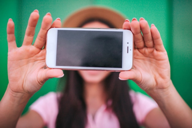 A picture of phone that girl holds in hands. it is white with dark screen.