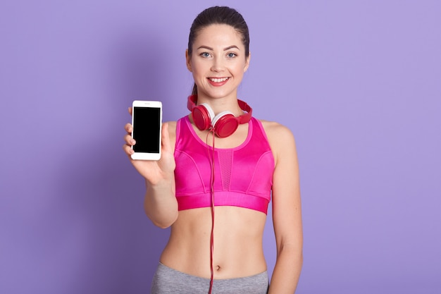 Picture of pleasant smiling cute young woman, holding smartphone, having headphones around neck