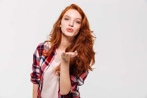 Picture of pleased ginger woman in shirt sends air kiss