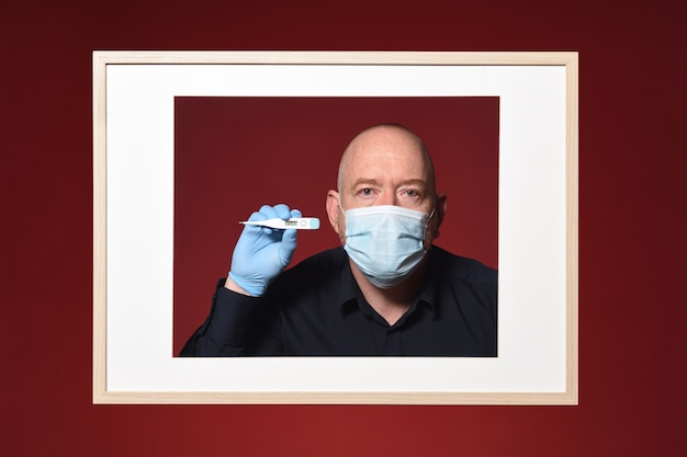 Picture of portrait of a man with gloves, mask and  thermometer on a red background