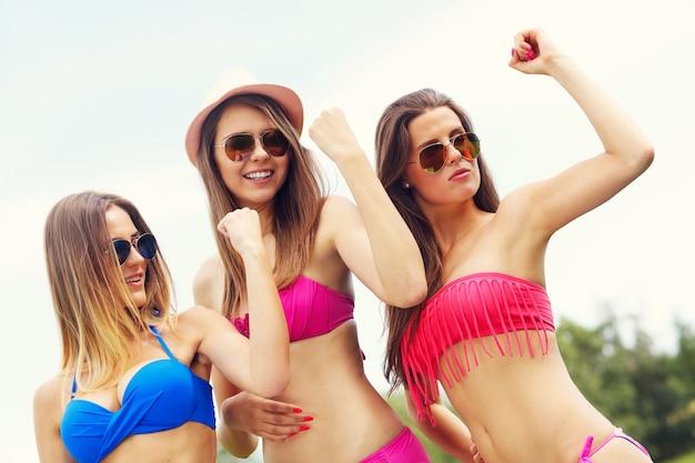 야외에서 근육을 보여주는 비키니 입은 여성 그룹을 제시하는 사진