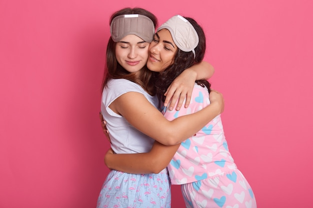 Picture of pretty beautiful good looking friendly sisters hugging each other, closing eyes, having facial expression, going to bed