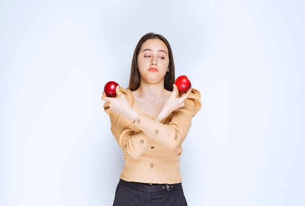 Immagine di una bella modella in piedi e in possesso di mele rosse fresche.