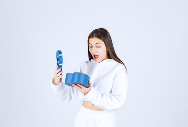 Immagine di un modello di ragazza piuttosto giovane che tiene una confezione regalo a forma di cuore.