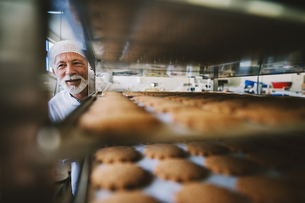 Picture of professional mature male baker man in white work uniform. standing in front of the shelves full with fresh baked cookies.