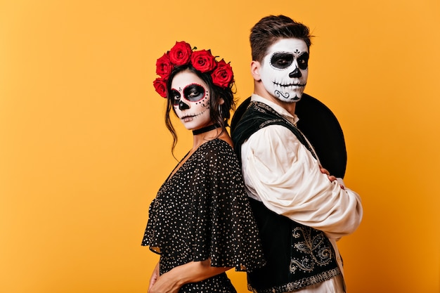 Picture of proud mexican couple in traditional clothes with painted faces. girl with roses in her hair poses with young man with sombrero behind his back.