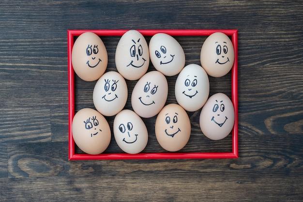 그림 빨간색 프레임과 어두운 나무 벽 배경에 웃고 있는 많은 재미있는 달걀이 닫힙니다. 계란 가족 감정 얼굴 초상화입니다. 개념 재미있는 음식
