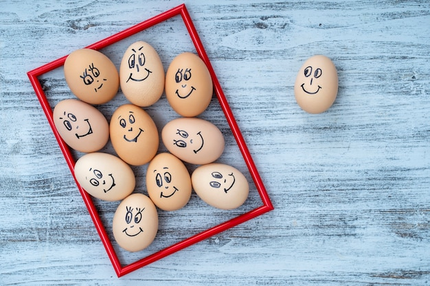 그림 빨간색 프레임과 흰색 나무 벽 배경에 웃고 있는 많은 재미있는 달걀을 닫습니다. 계란 가족 감정 얼굴 초상화입니다. 개념 재미있는 음식. 복사 공간