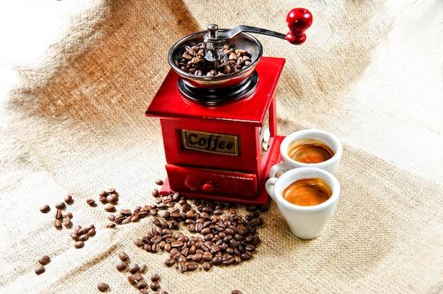 Picture of red vintage coffee grinder with two coffee cups