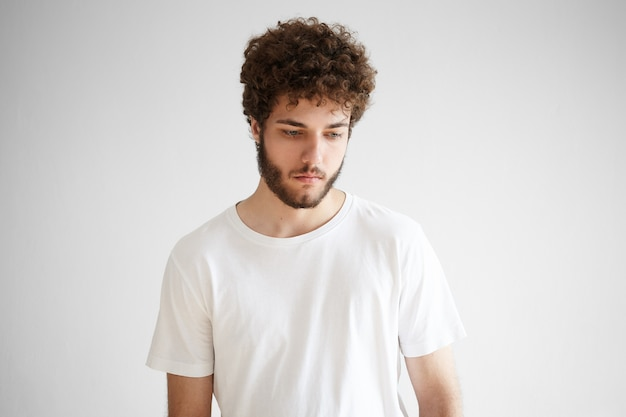 Picture of sad young european male with thick beard looking down having pensive deep in thoughts facial expression, thinking over problems, posing isolated against blank wall