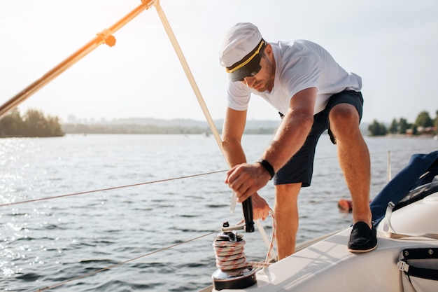 Picture of sailor stands on yacht and winds rope around. he is calm and concentrated. young man works hard. he prepares for sailing.