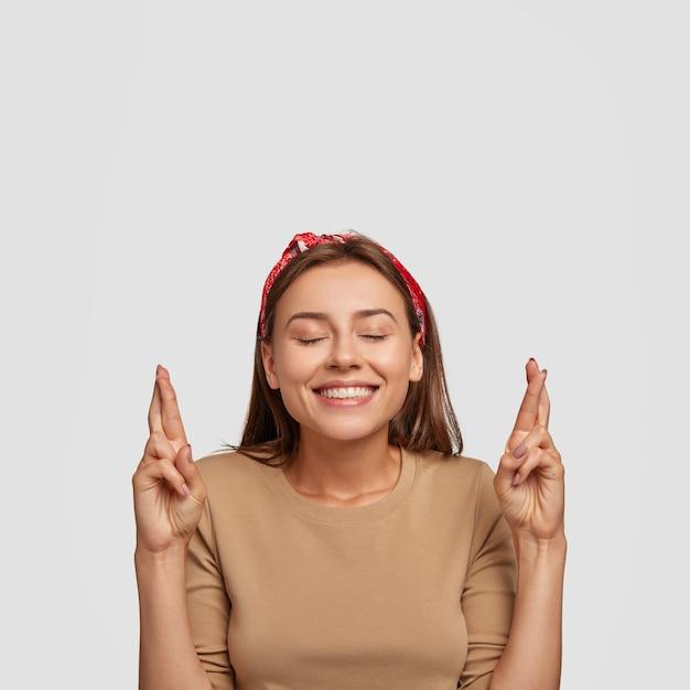 Foto di ragazza allegra soddisfatta con un sorriso amichevole, tiene gli occhi chiusi dal piacere