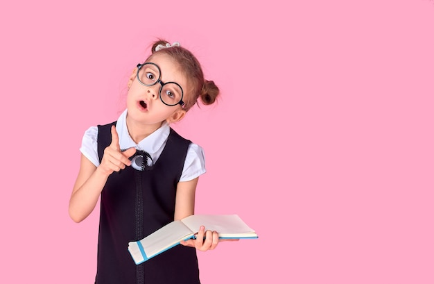 A picture of a schoolgirl with textbook pointing at something over isolate pink space