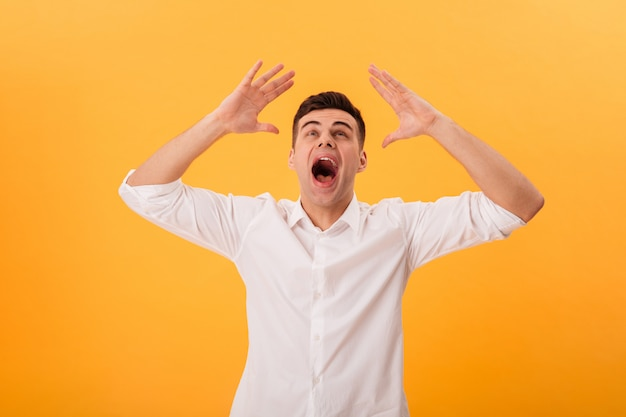 Picture of screaming man in white shirt looking up over yellow