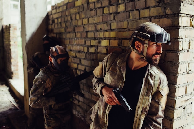 A picture of serious bearded man hiding behind wall and looking to the side. he has gun. other two men in maska are standing behind him. they are waiting for his command to start a fight.