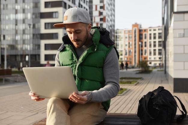 Immagine di giovane maschio serio concentrato con stoppie che navigano in internet, utilizzando la connessione wireless 4g sul laptop. libero professionista barbuto che lavora a distanza su gadget elettronici generici all'aperto nel paesaggio urbano