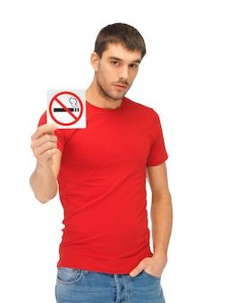 Picture of serious man in red shirt with no smoking sign.