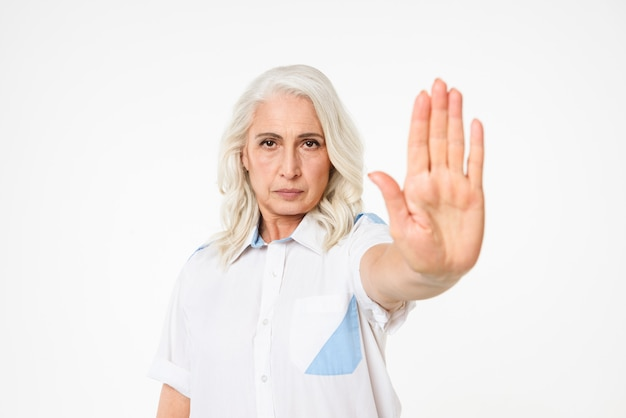 Picture of serious mature woman with grey hair looking strictly, expressing total rejection and gesturing to stop with hand, isolated over white wall