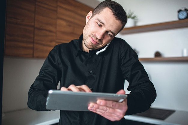 Picture of serious young businessman talking on phone and working on tablet. stand in kitchen alone. ceo company or successful manager manage business. productive efficient work.