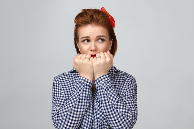 Picture of shocked attractive stylish young caucasian woman with finger hair looking away having scared expression, holding hands at her face, frightened with sudden terrifying sound, being home alone