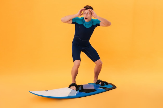 Picture of a shocked surfer in wetsuit using surfboard like on wave