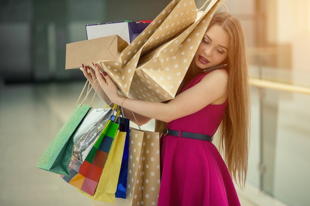 Picture of a shocked young brunette woman in white summer dress wearing sunglasses posing with shopping bags on pink.
