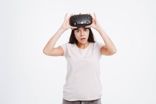 Picture of shocked young lady wearing virtual reality device .