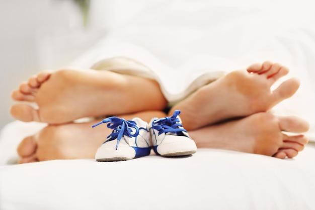 침대와 작은 아기 신발에서 쉬고있는 부부의 발을 보여주는 그림