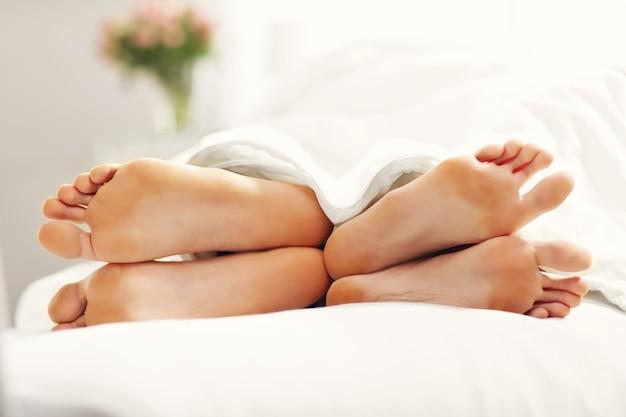 Фотография, показывающая ноги пары, отдыхающей в спальне