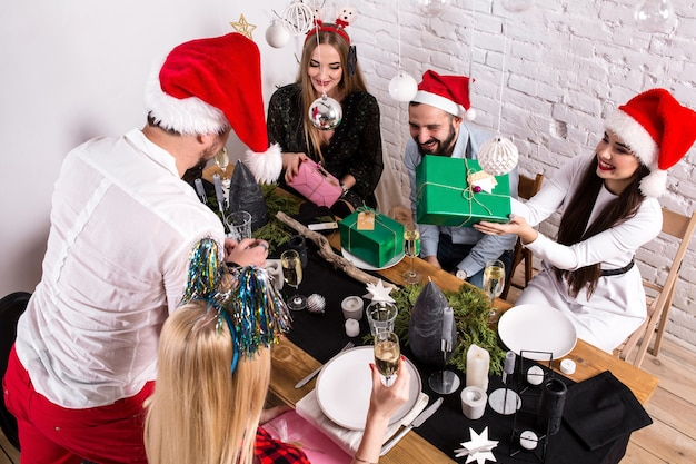 家でクリスマスを祝い、お互いにプレゼントを贈る友人のグループを示す写真