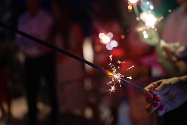 線香花火を楽しんでいる友人のグループを示す写真。