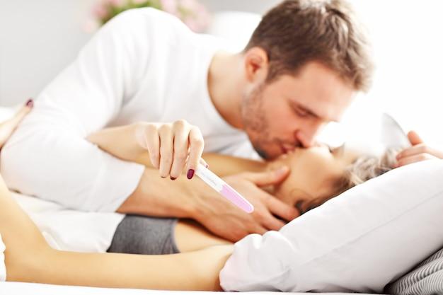ベッドで妊娠検査をしている幸せなカップルを示す写真